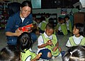 US Navy 090220-N-6692A-063 Aviation Ordnanceman Airman Francheska Montoya shares candy with a group of Thai kindergarteners.jpg