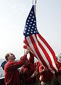 US Navy 090623-N-3235P-029 Chief Aviation Ordnanceman Victor Almodovar, left, helps Chief Aviation Ordnanceman Mark Seals, raise a flag honoring John Finn, the oldest living Medal of Honor recipient.jpg