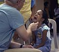 US Navy 090706-F-7923S-039 Cmdr. Matt Herzberg, a dentist embarked aboard the Military Sealift Command hospital ship USNS Comfort (T-AH 20), screens a young Nicaraguan girl to see how his team can help her.jpg