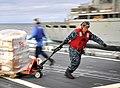US Navy 100319-N-4774B-210 Ship's Serviceman 2nd Class John Duran pulls a palette of supplies aboard the guided-missile cruiser USS Bunker Hill (CG 52).jpg