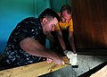 US Navy 100413-N-9301W-149 Cmdr. Robin Smith, left, executive officer of the guided-missile frigate USS Klakring (FFG 42), reinforces a floor support with the help of a fellow Sailor during a community service project.jpg