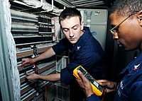 US Navy 100520-N-8913A-096 Interior Communications Electricians 3rd Class Rory J. Shisler, left, and Larry O. Hughes perform maintenance on the internal phone system aboard USS George H.W. Bush (CVN 77).jpg
