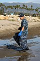 US Navy 111113-N-OM503-001 ire Controlman 2nd Class Duo Chen of Fort Lauderdale, Fla., searches for trash and debris during the community beach cle.jpg