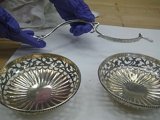 Polishing (metalworking) - A tarnished and unpolished silver bowl (left) and a polished silver piece (right). There is a visible difference in cleanliness and color. The piece held above the two bowls has also been polished. (These pieces are part of an 18th-century silver epergne in the collection of the Indianapolis Museum of Art).