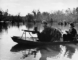 Vietnam War - Viet Cong with automatic weapons use leafy camouflage as they patrol a portion of the Saigon River in small boats.