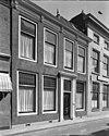 foto van Lijstgevel. Huis van parterre en verdieping. Deuromlijsting met verdiepte pilasters, gesneden deur en consoles onder de kroonlijst Lod. XIV