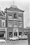 foto van Pand met twee verdiepingen en forse geblokte, in het midden verhoogde en met timpaan bekroonde kroonlijst onder laag schildak