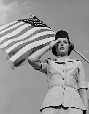 Women in the Air Force - A 1952 WAF officer candidate salutes in front of the American flag