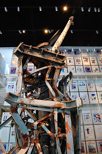 Aftermath of the September 11 attacks - Part of the North Tower's antenna mast displayed at the Newseum in Washington, D.C., behind it a panel of September 12 front pages from around the world