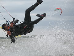 Kitesurfer wearing one-piece wetsuit, hanging from harness, separated from board.