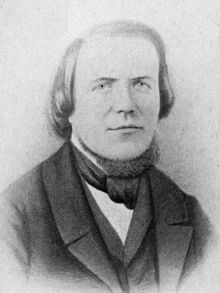 Head and bust of a man with a high forehead, hair reaching his shoulders, wearing a 19th-century three-piece suit and a cravat