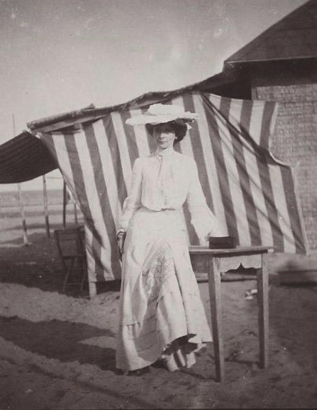 File:Woman in white before striped Canopy on Beach 1900s.jpg