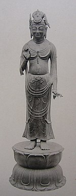 Frontal view of a statue on a pedestal with the left hand raised to breast height. The left hand carries a small object shaped like a vase or pot.