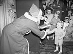 'Father Christmas' presents Winston Churchill Jr., the Prime Minister's grandson, with a gift at a Christmas party at Admiralty House in London, 17 December 1942. A13308.jpg