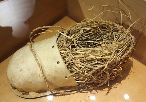 Ötzi shoe (replica), bearskin with deerskin upper, internal cage of twined linden bark, padded grass insulation - Bata Shoe Museum - DSC00004
