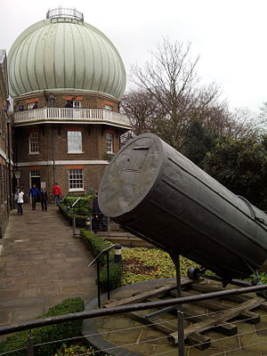"Telescope - The ""onion"" dome at the Royal Observatory, Greenwich housing a 28-inch refracting telescope with a remaining segment of William Herschel's 120-centimetre (47 in) diameter reflecting telescope (called the ""40-foot telescope"" due to its focal length) in the foreground."