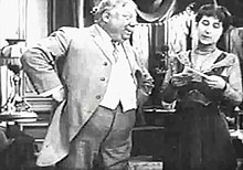 A black-and-white film still of an overweight man, hands on hips, staring at a woman to the right.
