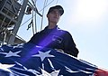 A U.S. Navy Sailor folds a battle ensign. (38492742830).jpg