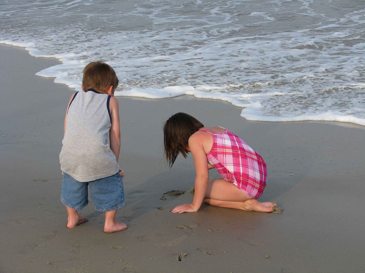Two little boys playing with sand on the beach wallpapers