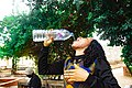 A lady gulping down water from a plastic container at IMSU Chaplaincy, Owerri.jpg
