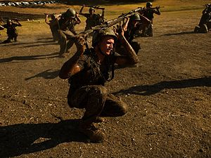 """Duckwalk - Airmen duck walk with their weapons held atop of their heads during the Air Force Pararescuemen Indoctrination """"Hell Week"""" Course, September 6, 2011, Lackland Air Force Base, Texas."""