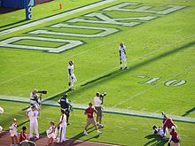 A pair of players wait at the end zone for a kickoff.