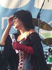 A dark-haired woman, wearing a black corset with red applications and a black cloak, holding a microphone in her left hand and touching her face with her right hand.