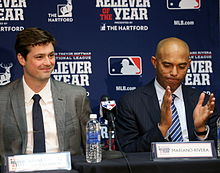 Andrew Miller and Mariano Rivera sit at a table at a press conference dressed in suits.