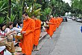 Another monk receives his rations from the faithful (14605819525).jpg
