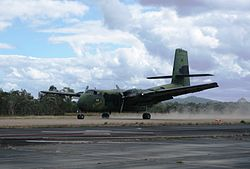Colour photograph of a camouflage painted aircraft driving along a dirt airstrip