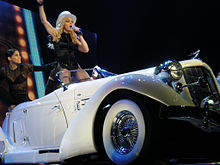 A group of performers on stage. Central to them, a blond female rides on a white car. She is flanked by dancers in black bondage style costumes. Behind them a background full of lights, is displayed.