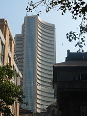 A skyscraper with curved walls and glass panes. A round building and a tree seen on its right side