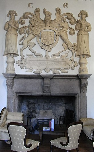 """Boringdon Hall - Fireplace on north wall of Great Hall, Boringdon, showing the royal arms of King Charles I, """"C.R."""", Carolus Rex, dated to 1640. The outside supporters are female figures of Peace (left) and  Plenty (right), holding a cornucopia. The royal motto is inscribed below within a strapwork frame. In the centre of the granite lintel is an escutcheon showing the arms of Parker"""