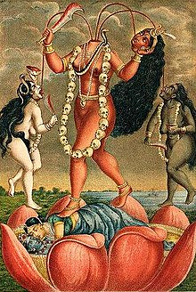 A decapitated, nude, fair goddess stands on a copulating couple inside a large lotus. She holds her severed head and a scimitar. Three streams of blood from her neck feed her head and two nude (one white, another black coloured) women holding a knife and a skull-cup, who flank her. The goddess wears a skull-garland, a serpent (across her chest) and various gold ornaments.