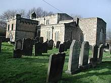 In the foreground are a number of graves marked by head-stones. Behind these is a small stone church building.