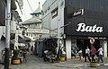 Collectie NMvWereldculturen, TM-20023926, Dia- Java, Semarang Toegangsweg naar stadskampong; op de achtergrond dak van de moskee. Rechts op de voorgrond bord met opschrift 17.8.92 (Indonesisch Onafhankelijksdag) ', Jaap de Jonge, 1993.jpg