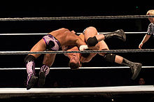 Two men in mid-air inside a wrestling ring.