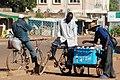 Cyclistes achetant les oeufs à un commerçant ambulant.jpg