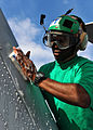 Defense.gov News Photo 101024-N-3374C-027 - U.S. Navy Petty Officer 2nd Class Antonio Hart assigned to Helicopter Maritime Strike Wing 70 scrubs down the tail of an MH-60R Seahawk.jpg
