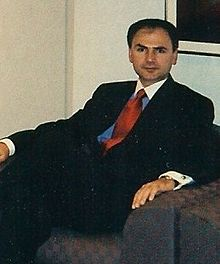dark-haired man resting in brown upholstered chair; wearing dark suit, blue shirt with white collar and red tie