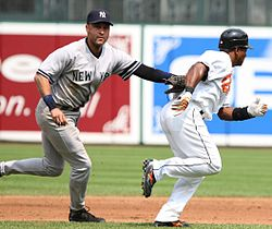 Jeter in a grey baseball uniform tags his glove to a baserunner from the opposing team.