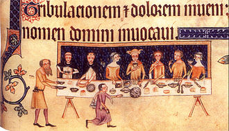 Luttrell Psalter - Sir Geoffrey Luttrell at table surrounded by his family and two Dominican friars. Two servants wait on them and others approach the table from the previous page; The tapestry behind has a field azure, semée of martlets argent, elements from the Luttrell coat of arms. Folio 208v.