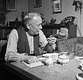 Dirk Nak met een sigaar in zijn handen in zijn woonkamer, Bestanddeelnr 252-9020.jpg