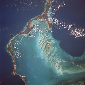 Eleuthera - Eleuthera Island is one of several within the archipelago surrounded by shallow seas, visible here as light blue. Mosaic patterns of sand waves built by sea bottom currents in the shallows stand out in stark contrast to the deep blue of the ocean depths of a thousand feet in the Exuma Sound.