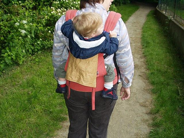 Enfant porté dans un porte-bébé dorsal