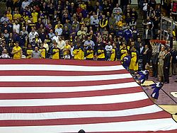 Michigan basketball team in gold (maize) uniforms during the national anthem