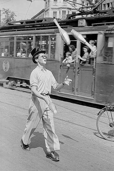 Vintage photo of a juggler in top hat and partial clown-face walking past commuters on a streetcar traveling in the opposite direction.