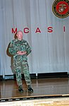 Gen. Alfred M. Gray stands on the stage of the Sukura theatre as he addresses a gathering of Air Station Iwakuni's Marines during his visit.jpg