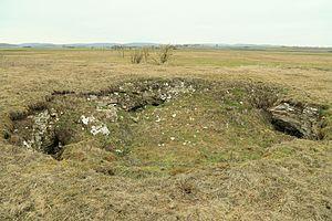De kalksteen lost op door het koolzuurhoudende water. Hierdoor ontstaan er gaten in het landschap. Deze gaten noem je dolinen.