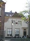 foto van Witgeverfd pand onder aan de voorzijde afgewolfd zadeldak gedekt met rode hollandse pannen. DE Welie